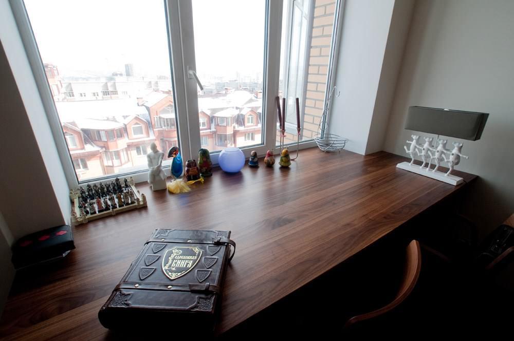 В жилой комнате можно использовать стол как продолжение подоконника, сделав неиспользуемое пространство полезным
