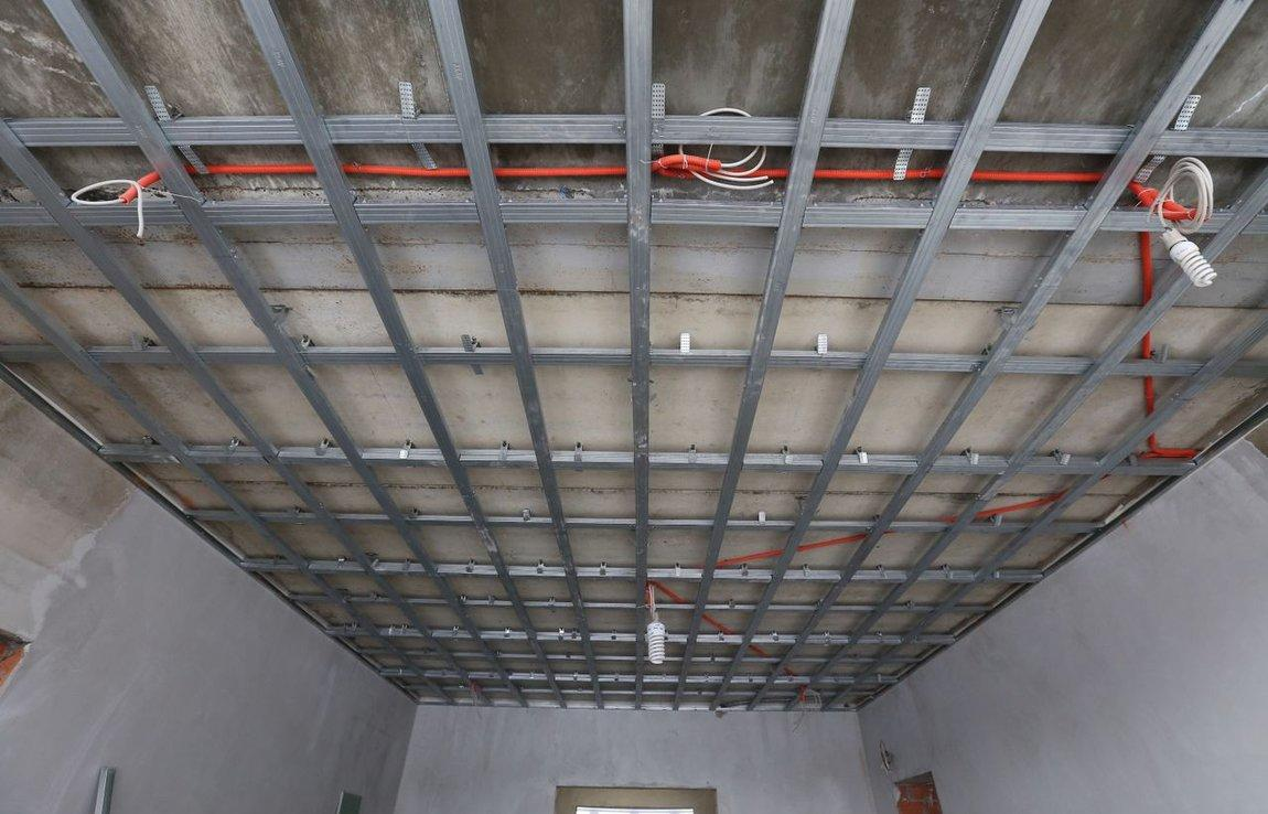 С помощью каркаса из металлических профилей можно с легкостью скрыть неровности потолка