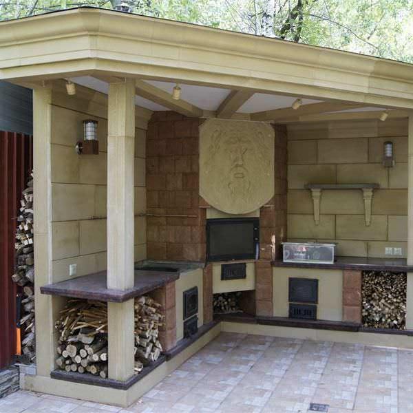 Дизайн полуоткрытого кухонного помещения можно обустроить, отталкиваясь от главного его элемента – камина или печи