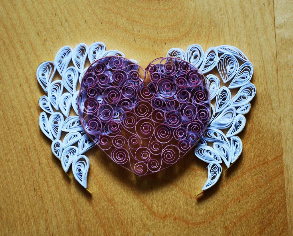 Оригинальным решением является создание сердца в технике квиллинг, оснащенное ангельскими крыльями