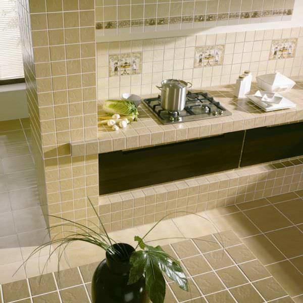 Плитка на полу кухни-гостиной должна ограничиваться только зоной кухни, в гостиной это будет попросту неуместно и неудобно