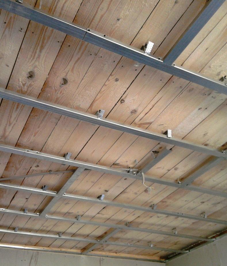 Перед установкой гипсокартонного потолка следует правильно смонтировать каркас, учитывая особенности деревянного потолка