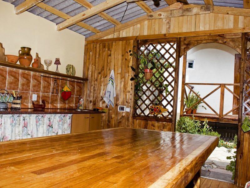 «Деревянный» интерьер летней кухни частного дома во многом превосходит другие виды оформлений
