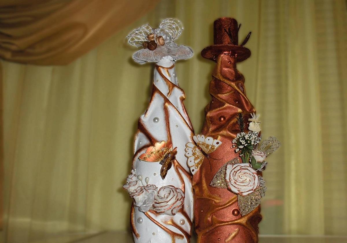 Отличным подарком на свадьбу являются бутылки, украшенные в технике декупаж с помощью колготок в виде дамы и мужчины в шляпе
