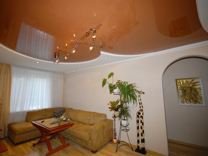 Сделать гостиную красивой и современной можно при помощи яркого натяжного потолка