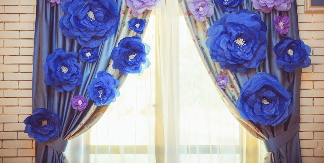 Гофрированные цветы лучше выполнять в ярких цветах, а повесить их можно на шторах