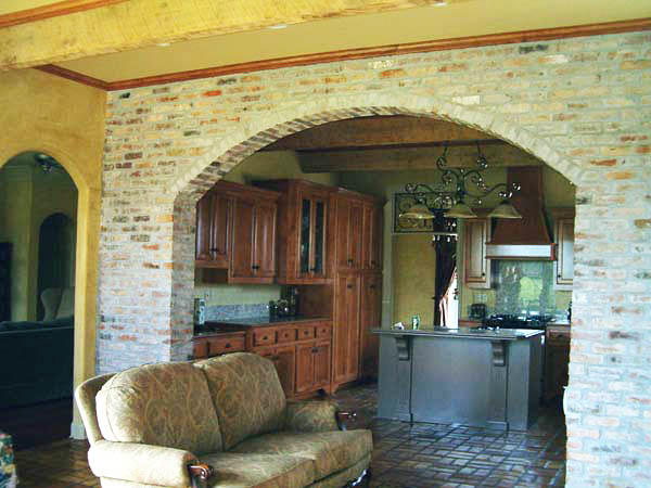 В качестве перегородки между кухней и гостиной из кирпича может выступать и арка, которая будет визуально делить пространство