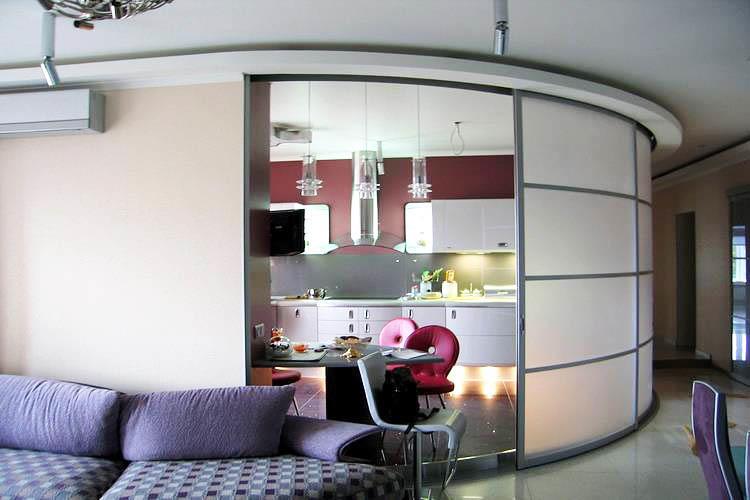 Радиусные раздвижные перегородки между кухней и гостиной будут очень уместны в загородном доме