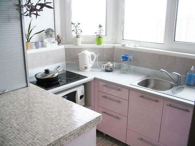 После объединения кухни с балконом, рабочую зону можно вынести именно туда. При этом холодильник и прочую технику можно оставить в кухне. Такое решение позволит грамотно распорядиться пространством, к тому же, в маленькой кухне такой вариант будет и вовсе единственным правильным