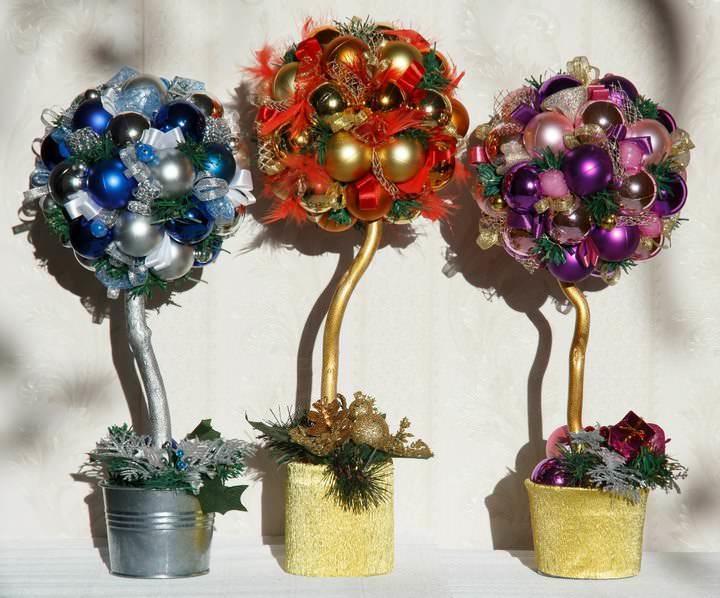 Блеск и искрящийся декор – основные качества новогоднего топиария. Деревце можно покрыть золотом или серебристой краской, визуально объединив все элементы оформления воедино