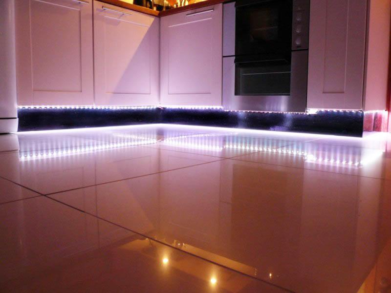 Если пол на кухне глянцевый, то не рекомендуем использовать светодиодную подсветку снизу шкафов в первоначальном виде. Лучше ее доработать, поместив в корпус с матовым стеклом. В таком случае на полу не будут отражаться светодиоды и подсветка будет мягкой и ненавязчивой