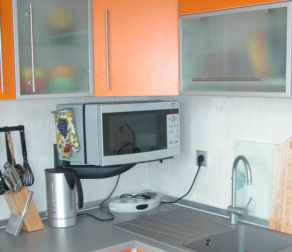 Полка может крепиться специальным кронштейном. В случае как на фото, крепление занимает минимум места и идеально вписывается в дизайн кухонного гарнитура