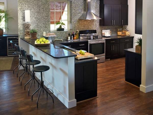 Довольно распространенным решением для угловой кухни с барной стойкой является использование стойки в качестве зонатора двух объединенных помещений