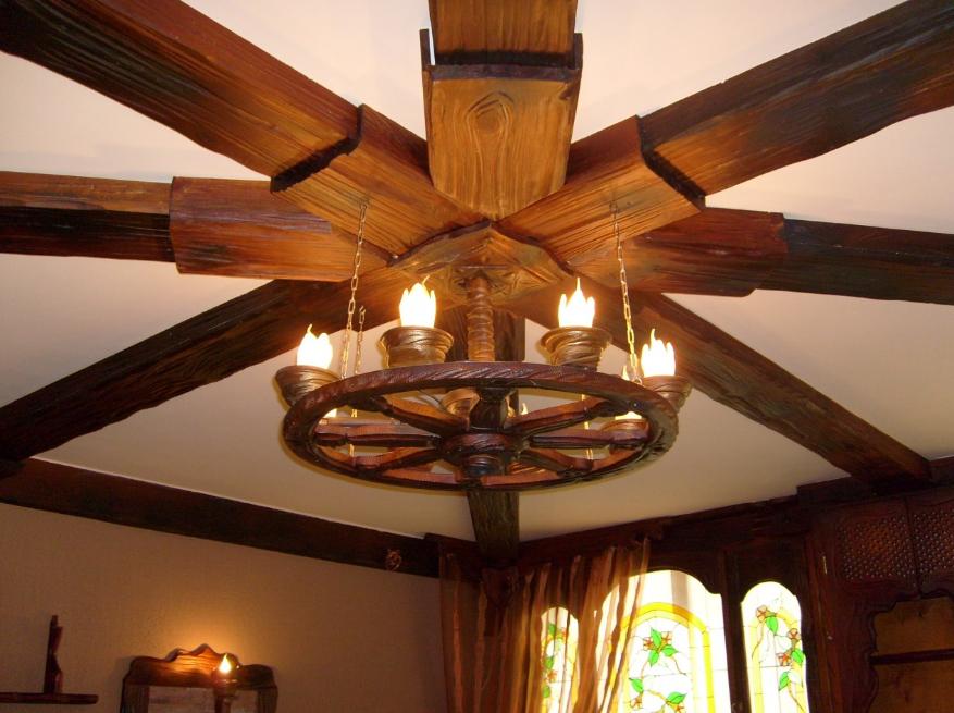 Оформить потолок под старину можно с помощью объемных деревянных балок, на которые рекомендуется повесить старинную кованную люстру