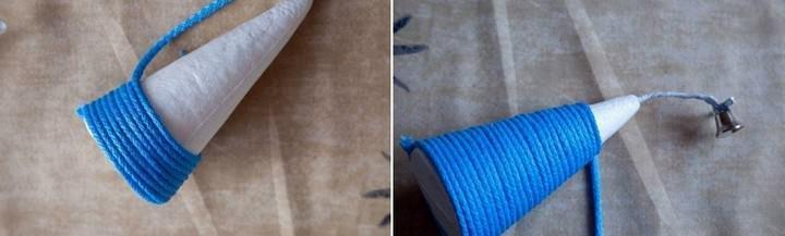 Обматываем основание шнуром вплотную, каждый ряд закрепляя клеем. В верхушку конуса вставляем проволоку с колокольчиком, закрепив ее клеем