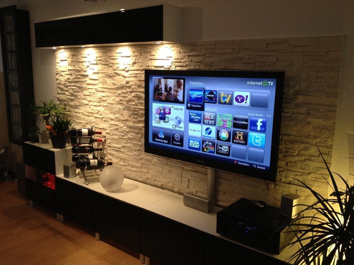 Телевизор в зале можно поставить на стенку или подвесить с помощью специального крепления