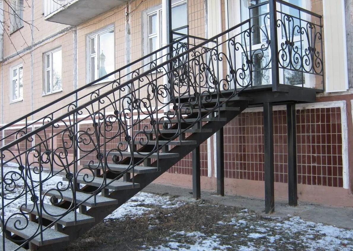 Улучшить эстетические качества уличной металлической лестницы можно с помощью перил с кованными элементами