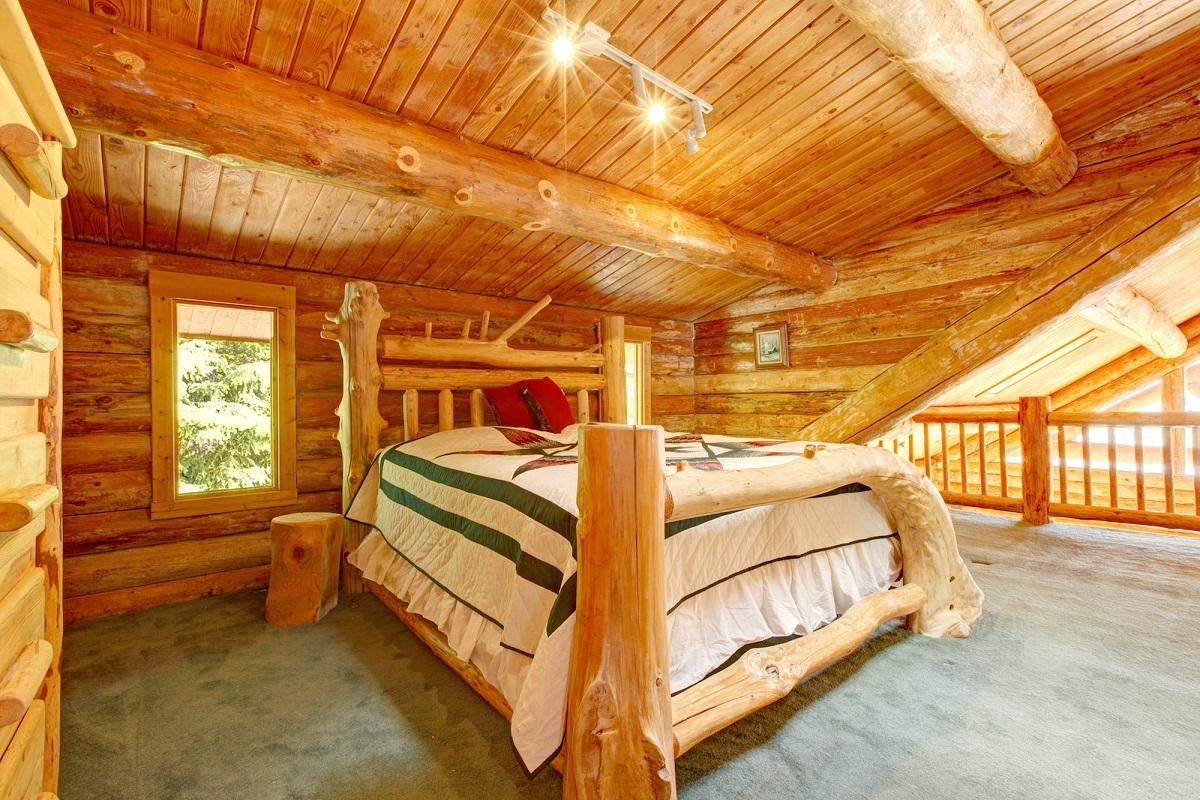 Потолок из натурального дерева в виде реек, покрытый лаком, хорошо сохраняет тепло и красиво выглядит