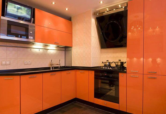 Зону фартука в оранжевой кухне можно отделать плиткой как темного, так и светлого оттенка