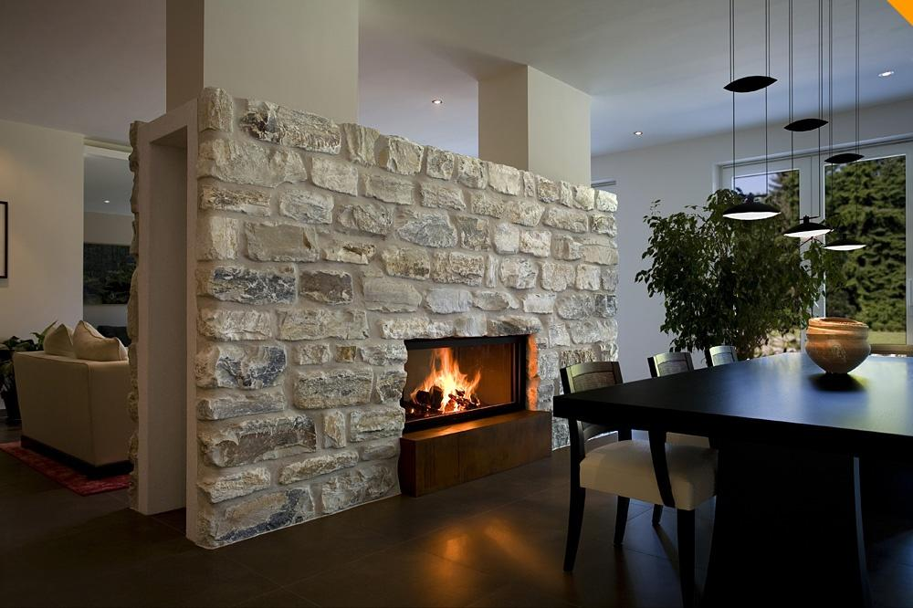Камин из камня великолепно смотрится в деревянных помещениях, загородных дачах, дополняя современный стиль и в то же время, придавая немного первобытности помещению