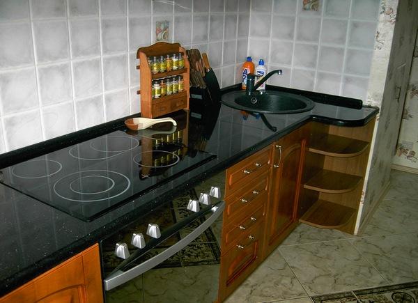 Чёрная столешница из гранита на кухне отлично смотрится с гарнитуром из массива дерева